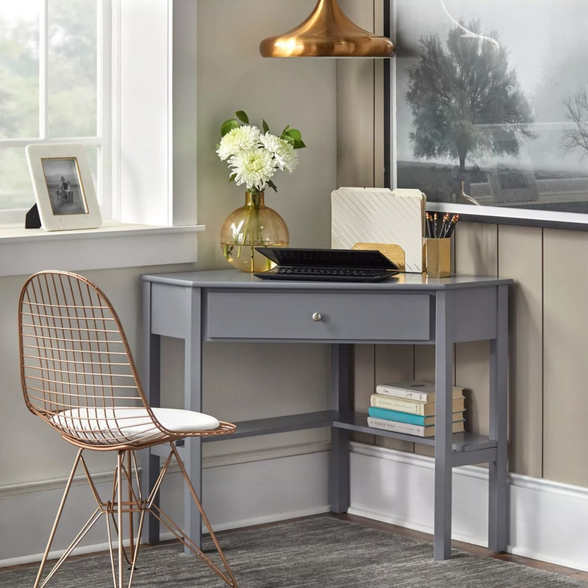 The corner desk in gray holding a laptop, vase, and cup of pencils