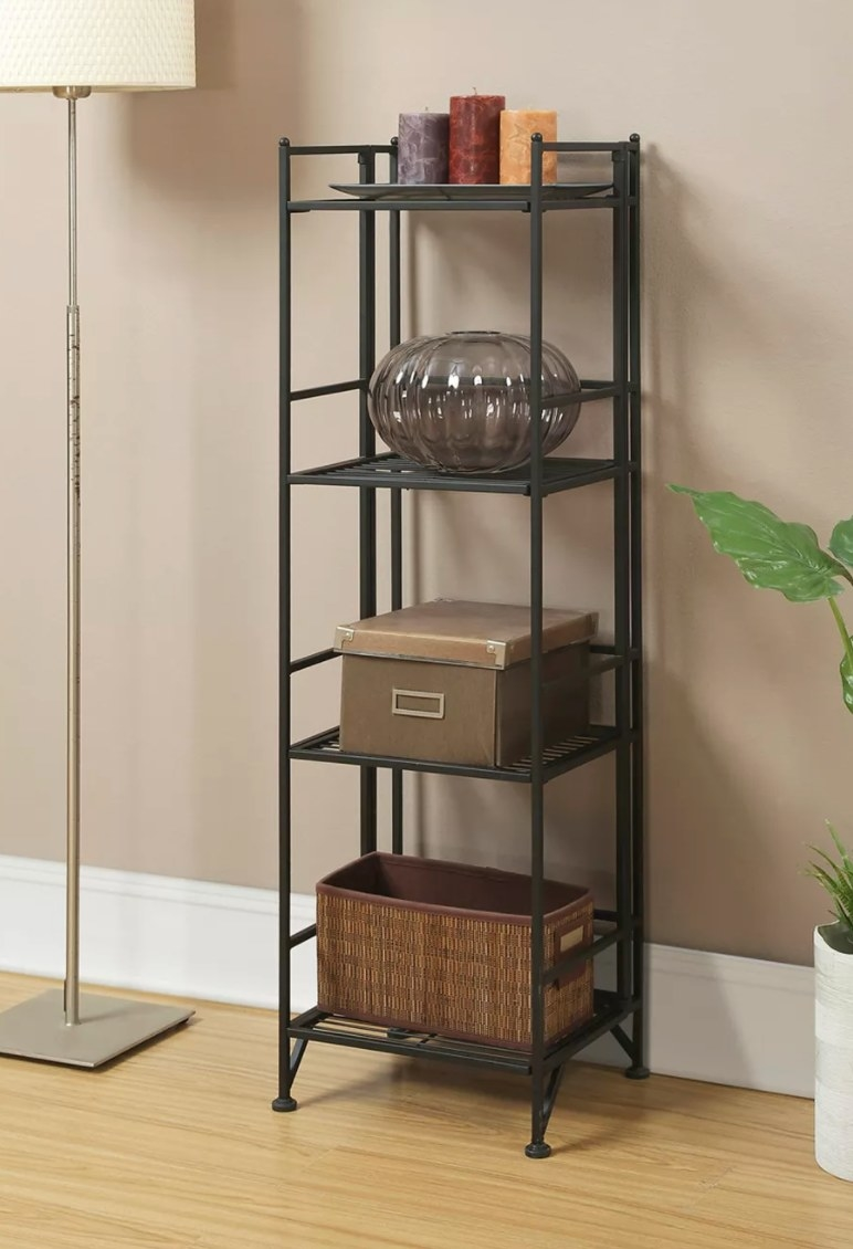 The four-tier folding metal shelf holding candles, a vase, and baskets