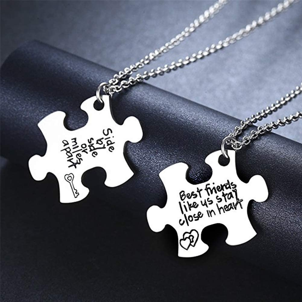 A pair of necklaces with puzzle piece pendants
