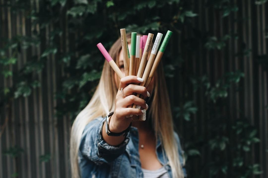 A person holding up a bundle of bamboo toothbrushes