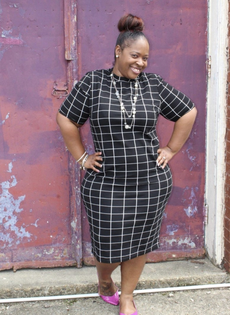 A person wearing a black geometric patterned dress
