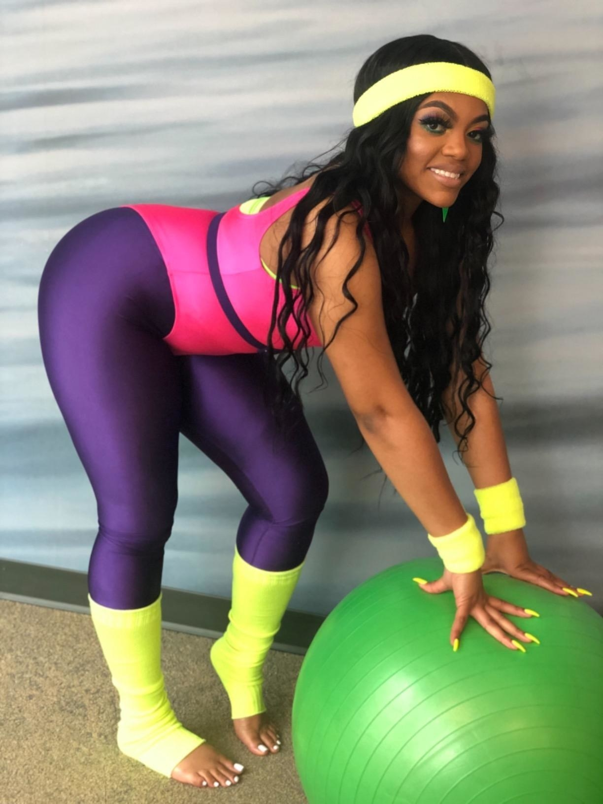 reviewer wearing the purple romastory metallic leggings with an 80s inspired workout fit
