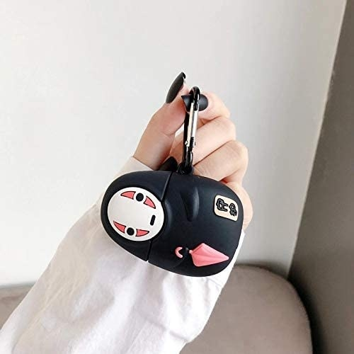 A person holding the airpods case shaped like No-Face from Studio Ghibli's Spirited Away