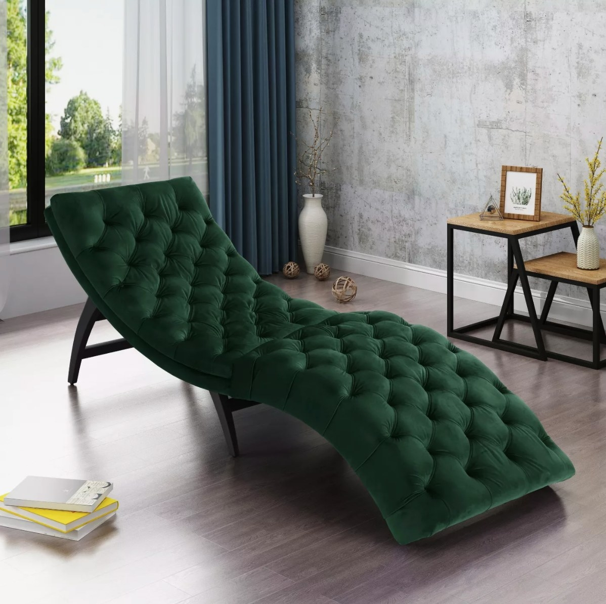 The tufted chaise lounge in emerald next to a slack of books and wood end table