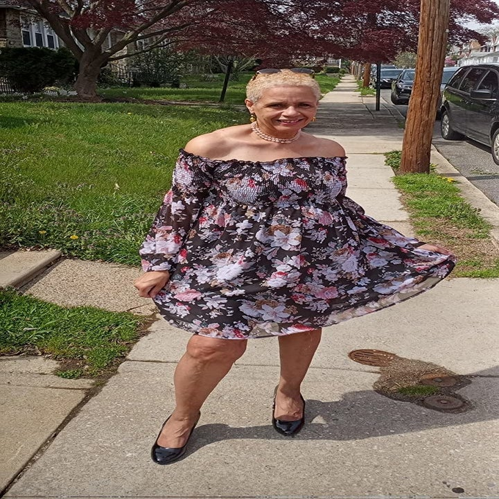 reviewer wearing the dress in black with pink and white flowers on it