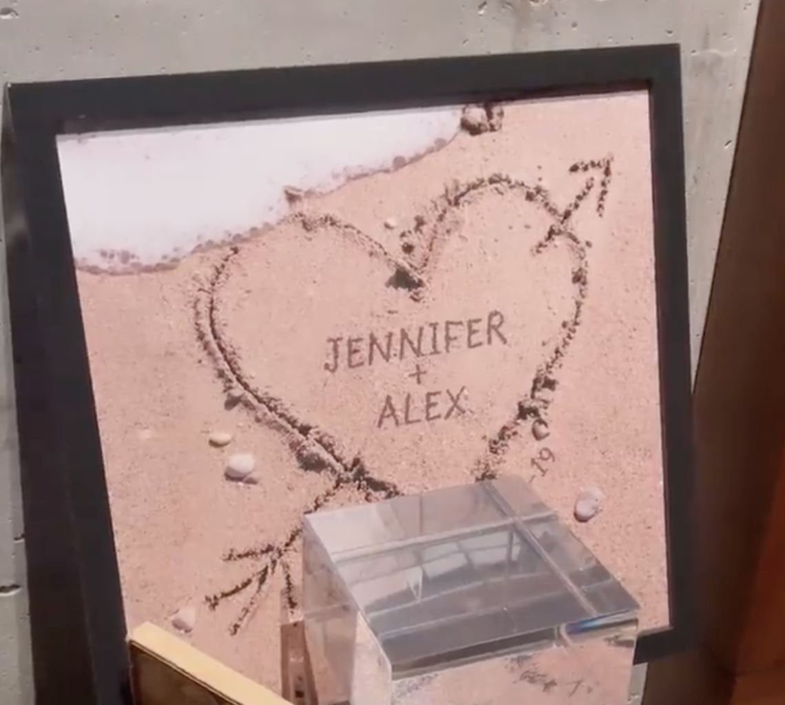 """Framed photo of """"Jennifer + Alex"""" in a heart in the sand"""