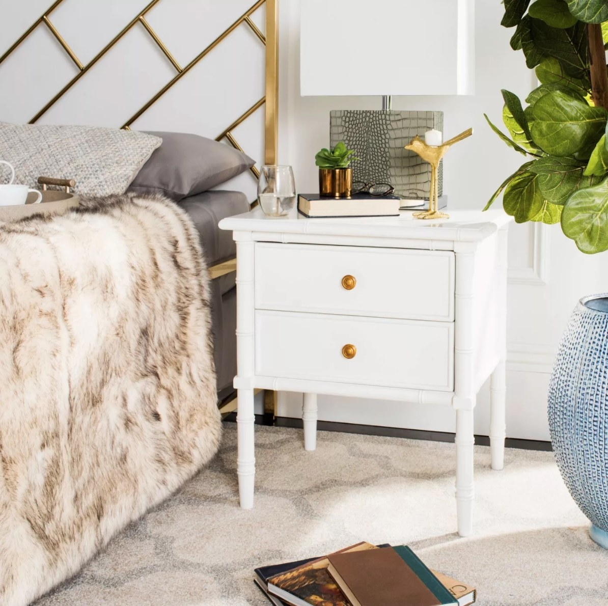 The two drawer nightstand in white holding a glass of water, plant, book, and lamp
