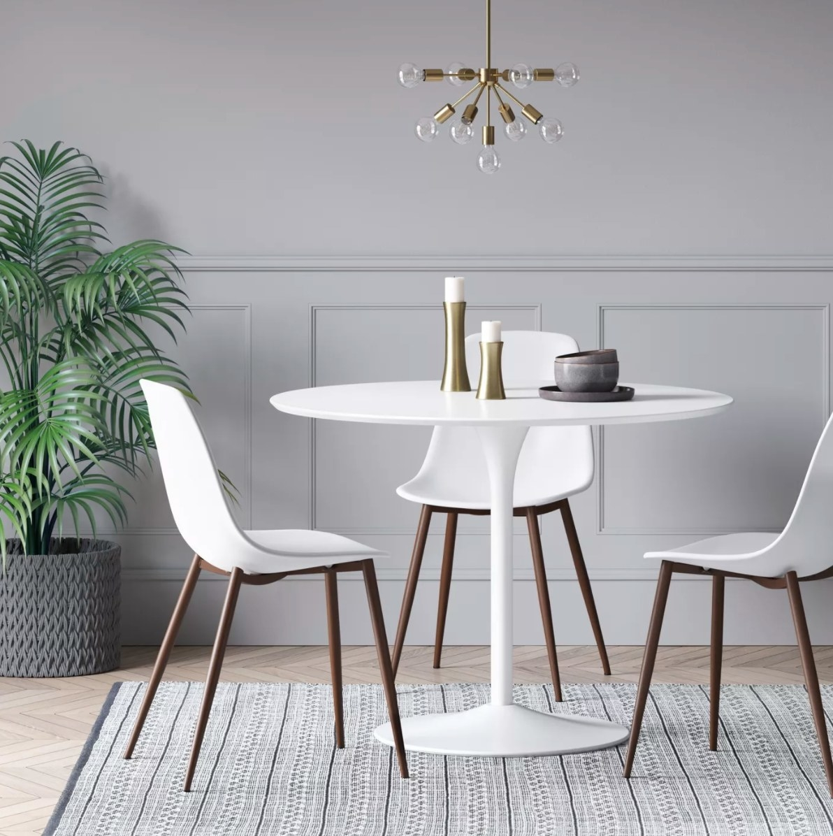The round dining table with a metal base in white holding candle sticks