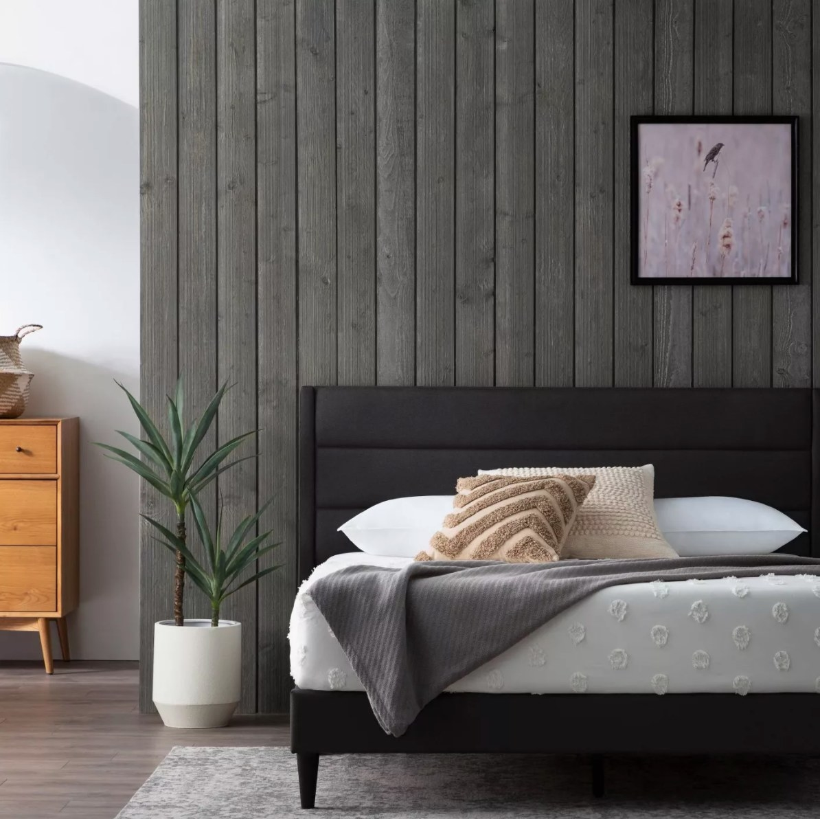 The upholstered bed in charcoal with accent pillows and a blanket drapped across