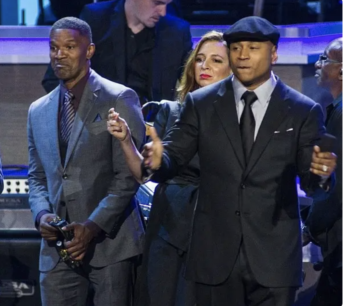 Jamie Foxx and LL Cool J dance onstage wearing suits