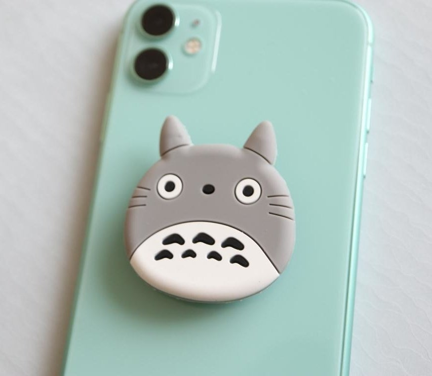 A totoro-shaped popsocket on a vibrant phone case