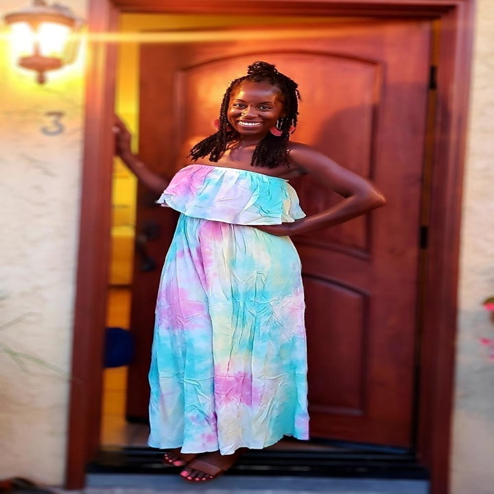 a reviewer wearing the dress in pink, blue, and yellow tie-dye