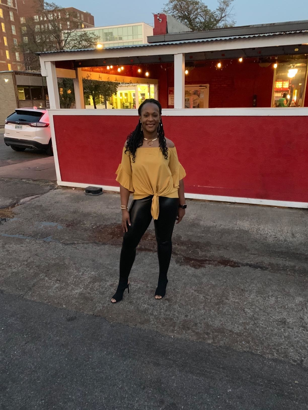 reviewer wearing the black faux leather leggings with a yellow top outside of a restaurant