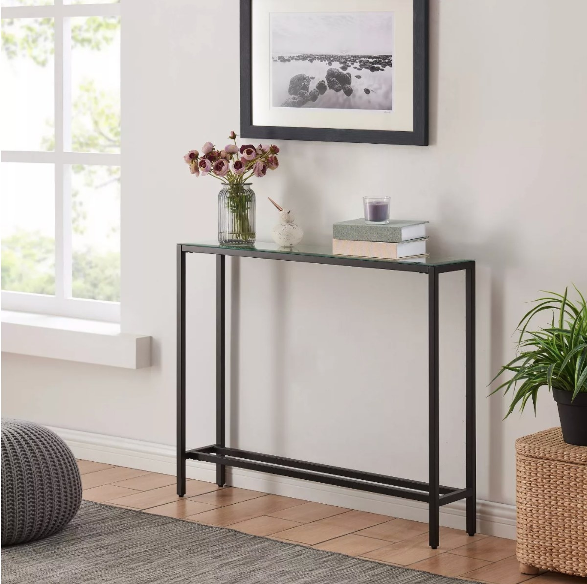 The narrow console table in black with a glass top holding books, candles, and flwoers