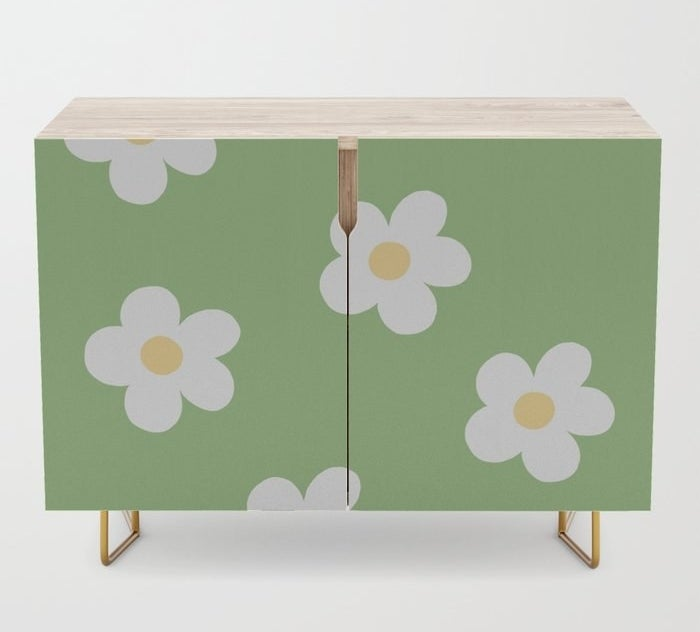 a green, daisy-covered credenza with yellow legs