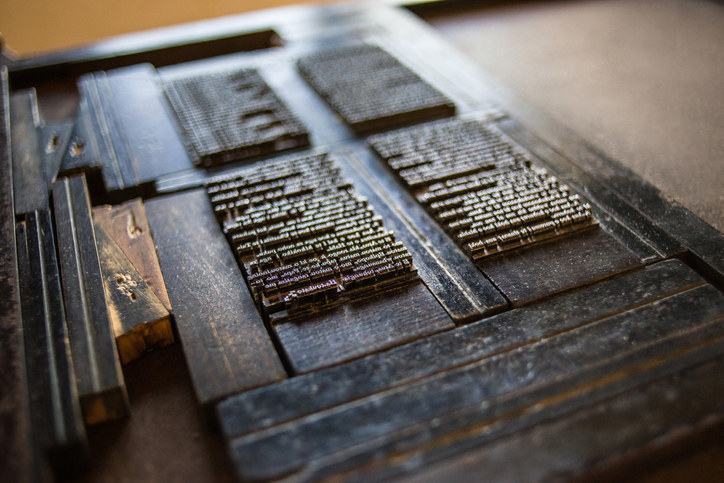 An old-fashioned printing press with words laid out