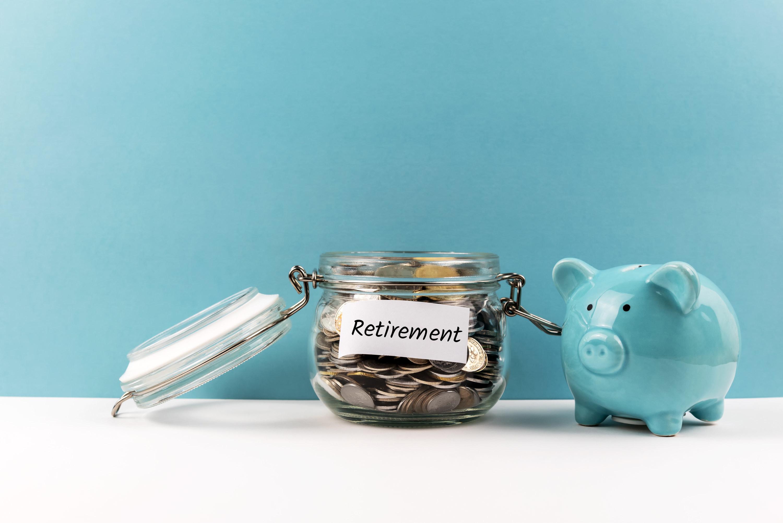 "Change jar labeled ""retirement"" next to a blue piggy bank"