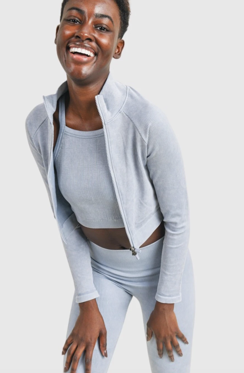 model in light blue cropped front-zip jacket with matching ribbed crop top and leggings
