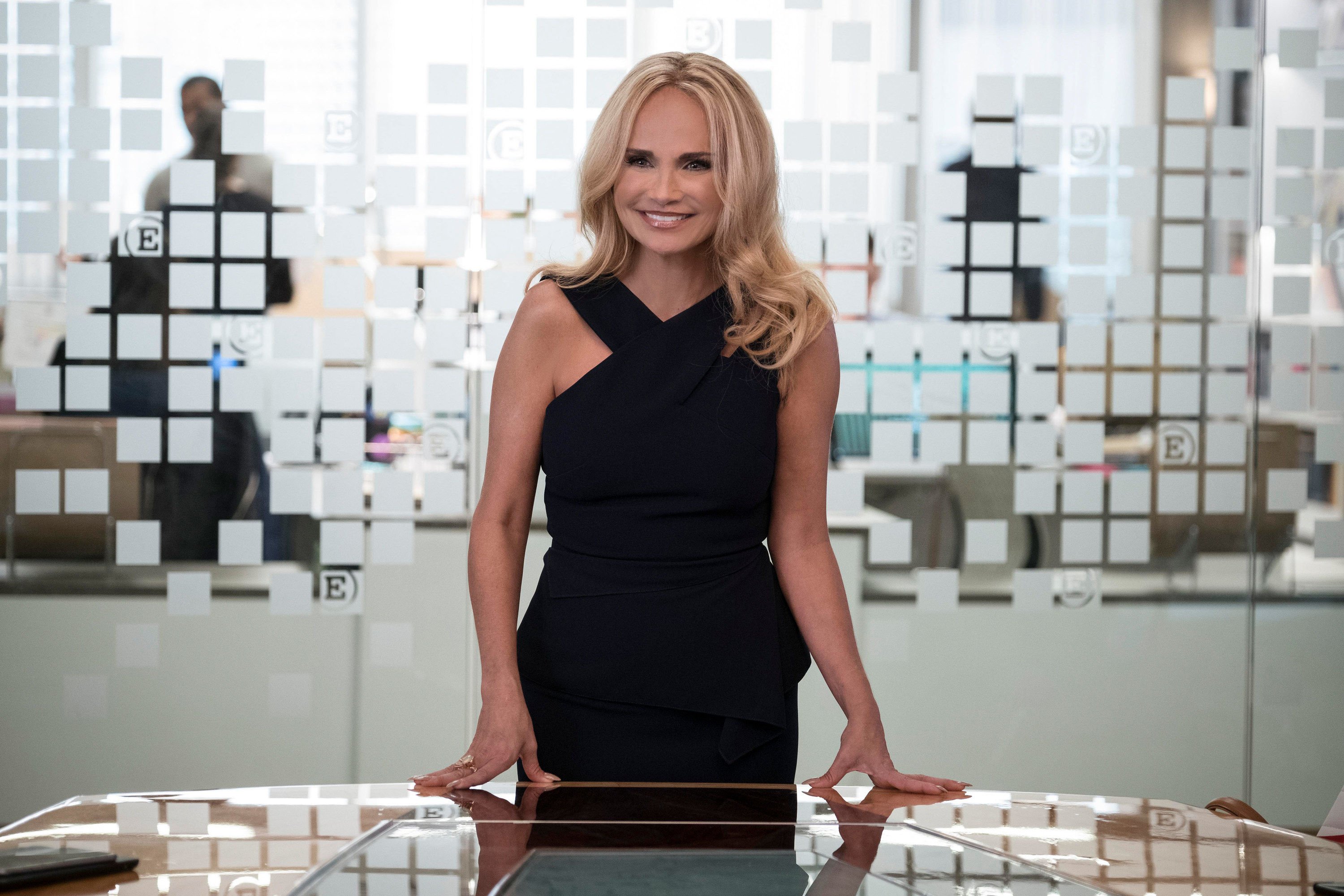 Kristin Chenoweth's standing the head of a table during her guest appearance on Younger