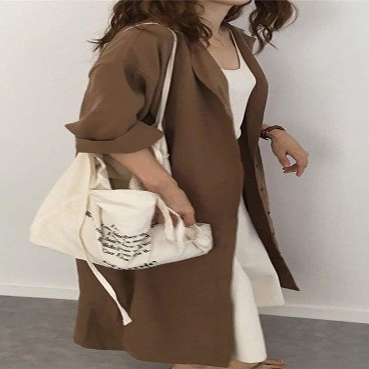 Model wearing brown maxi dress open like a jacket