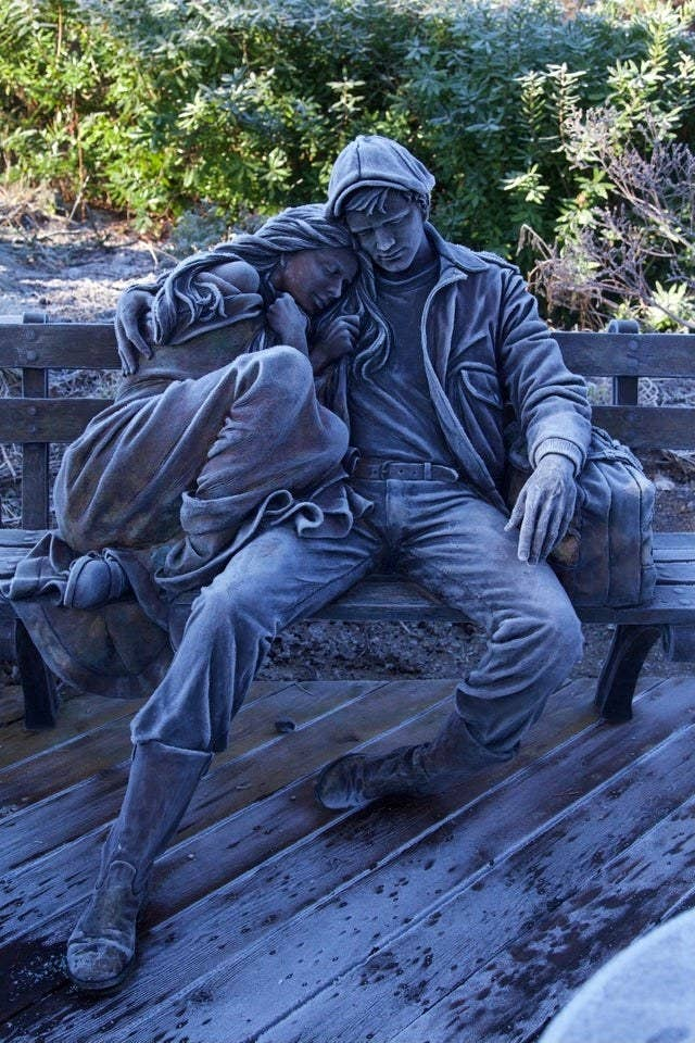 A sculpture of a man holding a woman, sitting on a bench dusted in frost that gives it coloring to look like a pencil drawing
