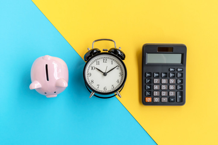 a piggy bank, clock, and calculator on bright background