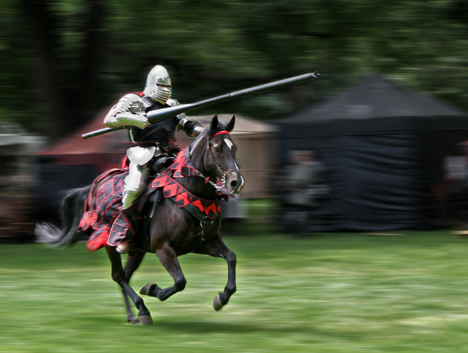 A knight in armor riding a horse and carrying a large lance