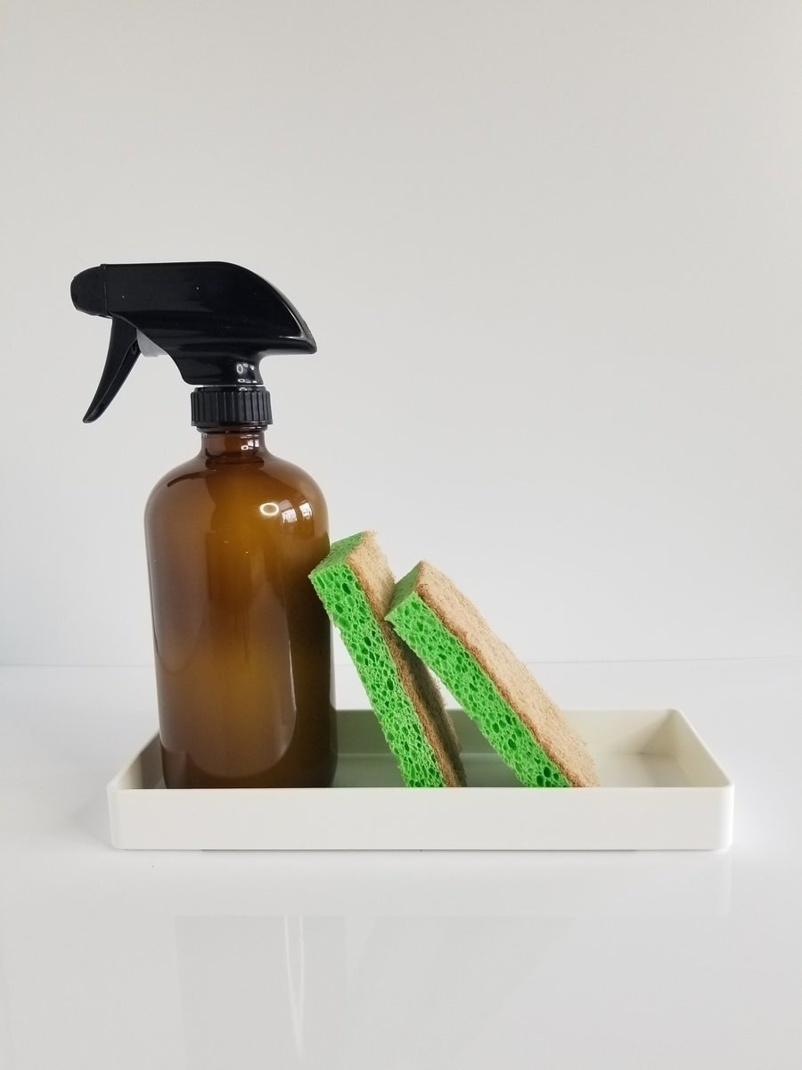 a brown glass bottle with two coconut husk sponges on a white tray