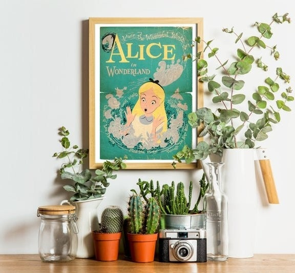 An alice in wonderland poster near some plants and knick knacks on a counter