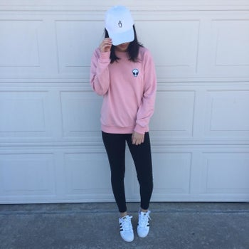 Reviewer wears same style sweatshirt in a pink color with a white baseball cap and leggings