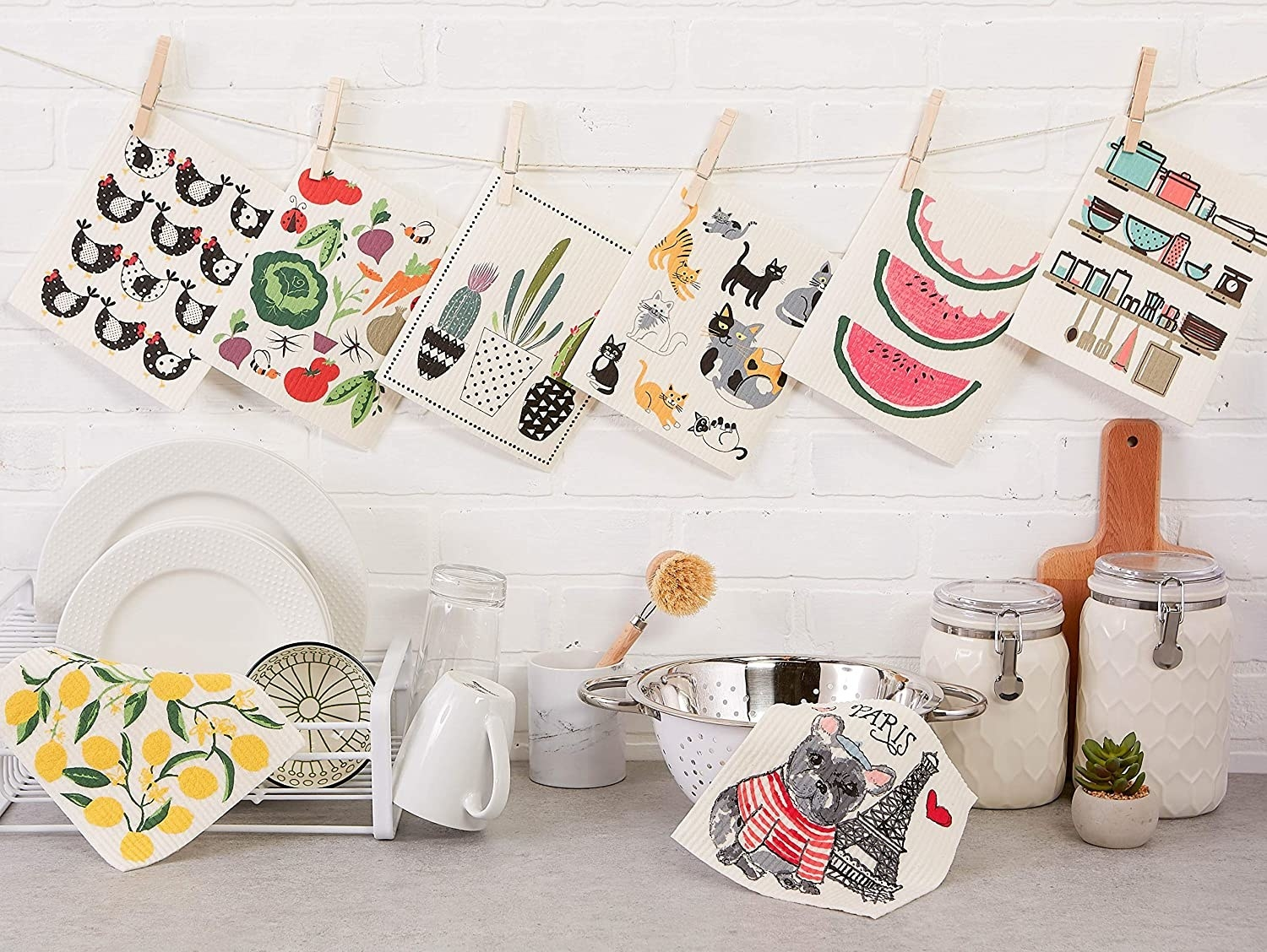 eight kitchen towles with various designs hanging up over a kitchen counter