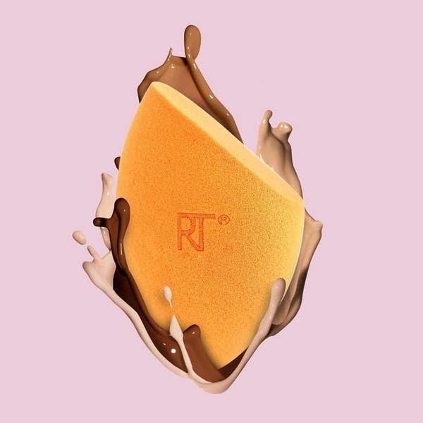 floating orange makeup sponge with foundation on it
