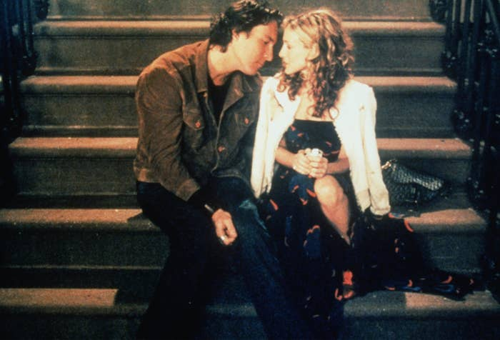 Carrie and Aidan sit on the steps of a building together