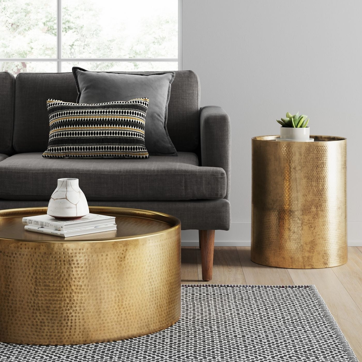 gold cylinder drum accent table with a small plant on top, next to a couch and gold coffee table