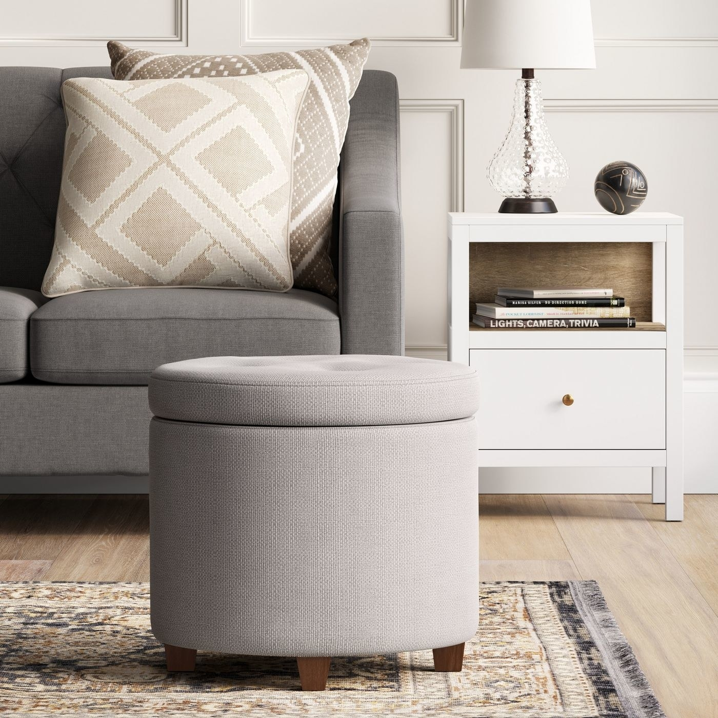round light grey tufted storage ottoman with a lid and wood legs, in a living room