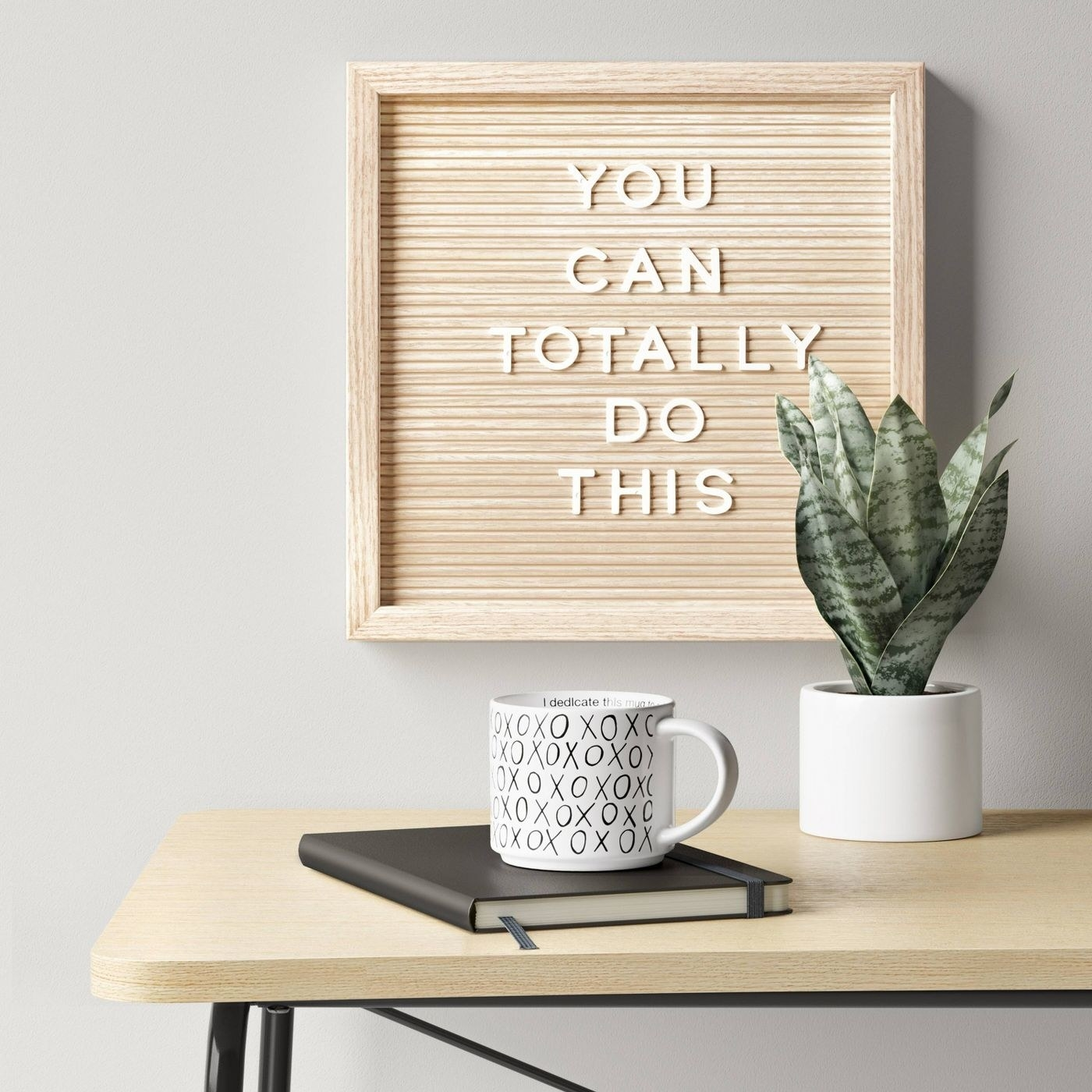 "wood letterboard with white letters spelling out ""you can totally do this"", hanging on a wall above a table"