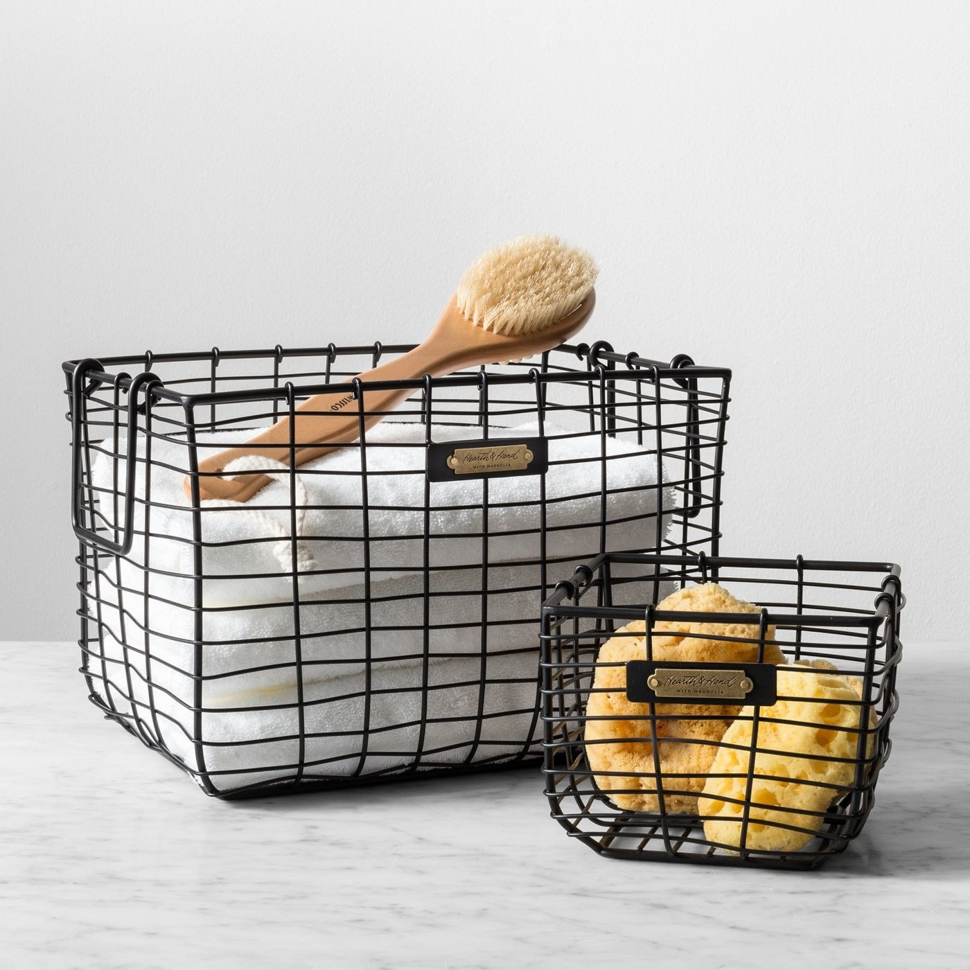 two wire storage baskets filled with bath accessories and towels