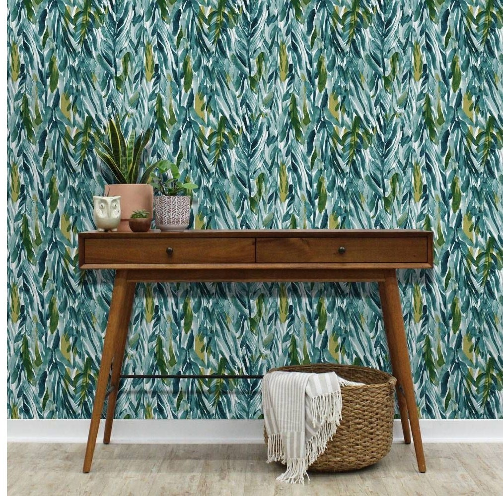 blue and green leaves print wallpaper on w wall behind a wood console table