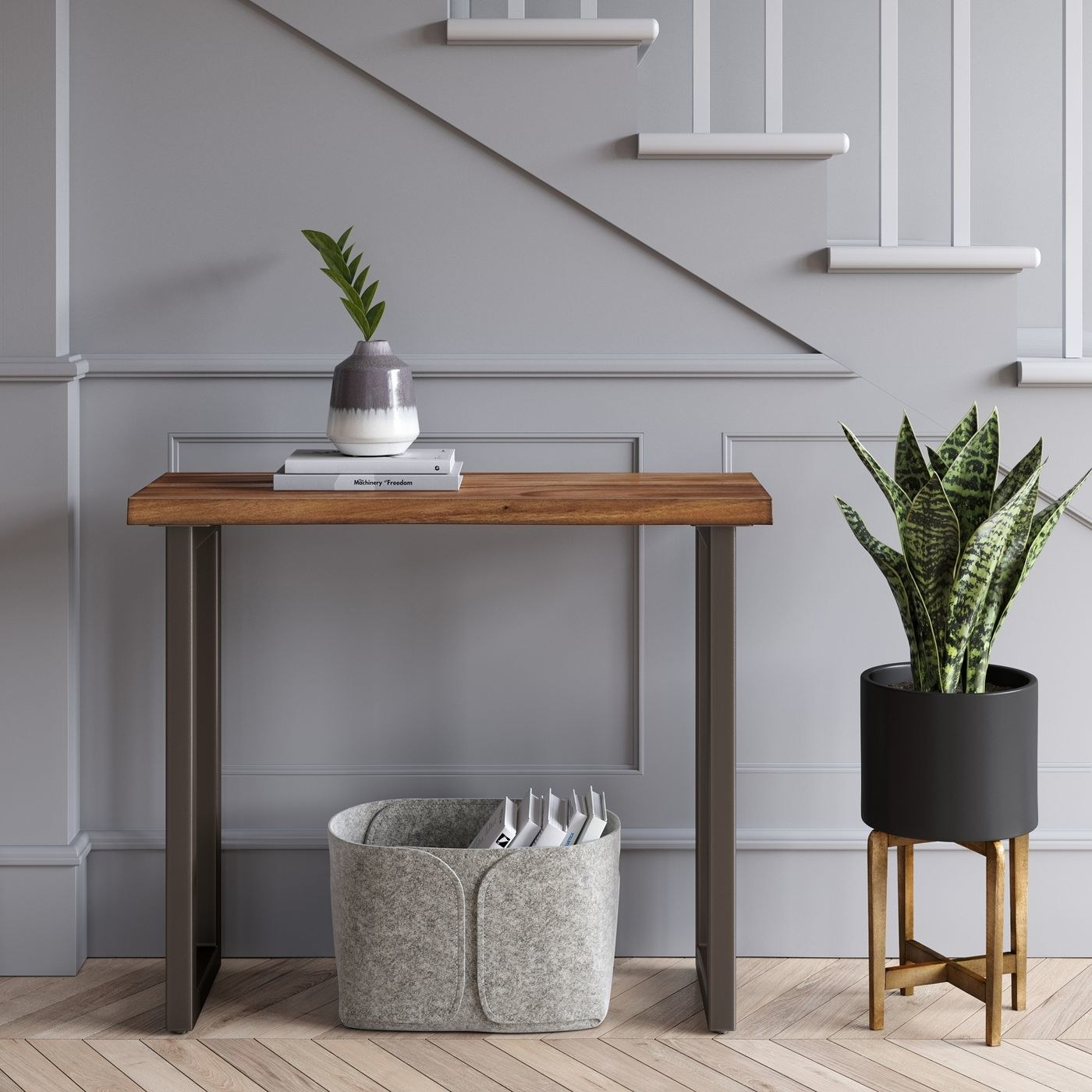 wood console table with metal legs against a wall with storage basket underneath and plant on top