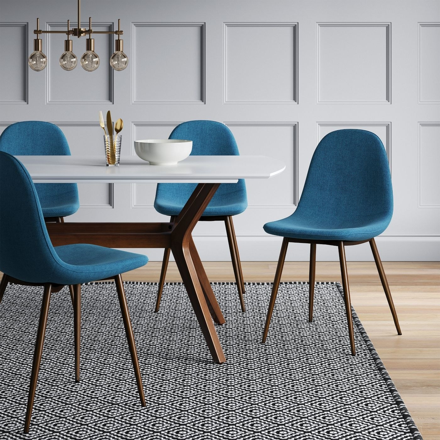 four teal upholstered dining chairs with wood legs around a white table