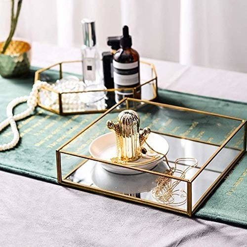 A gold-rimmed vanity tray on a table