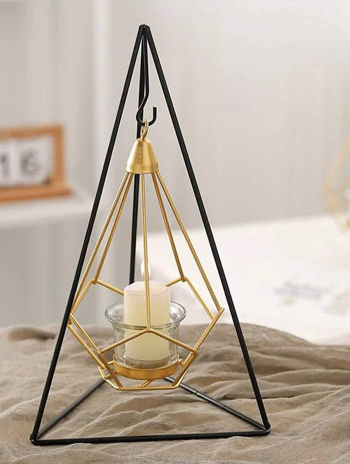 A geometric candle holder with a candle in it