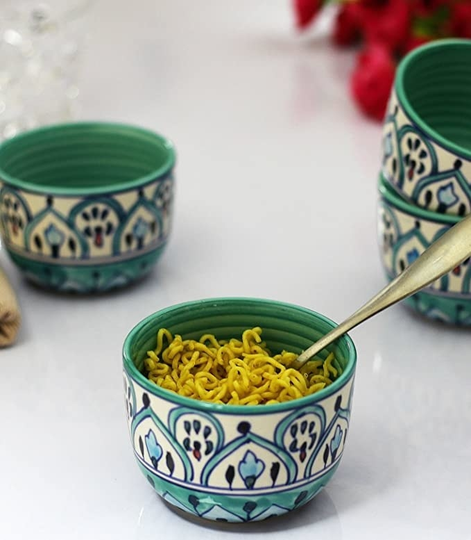 Blue and teal ceramic bowls with noodles in them