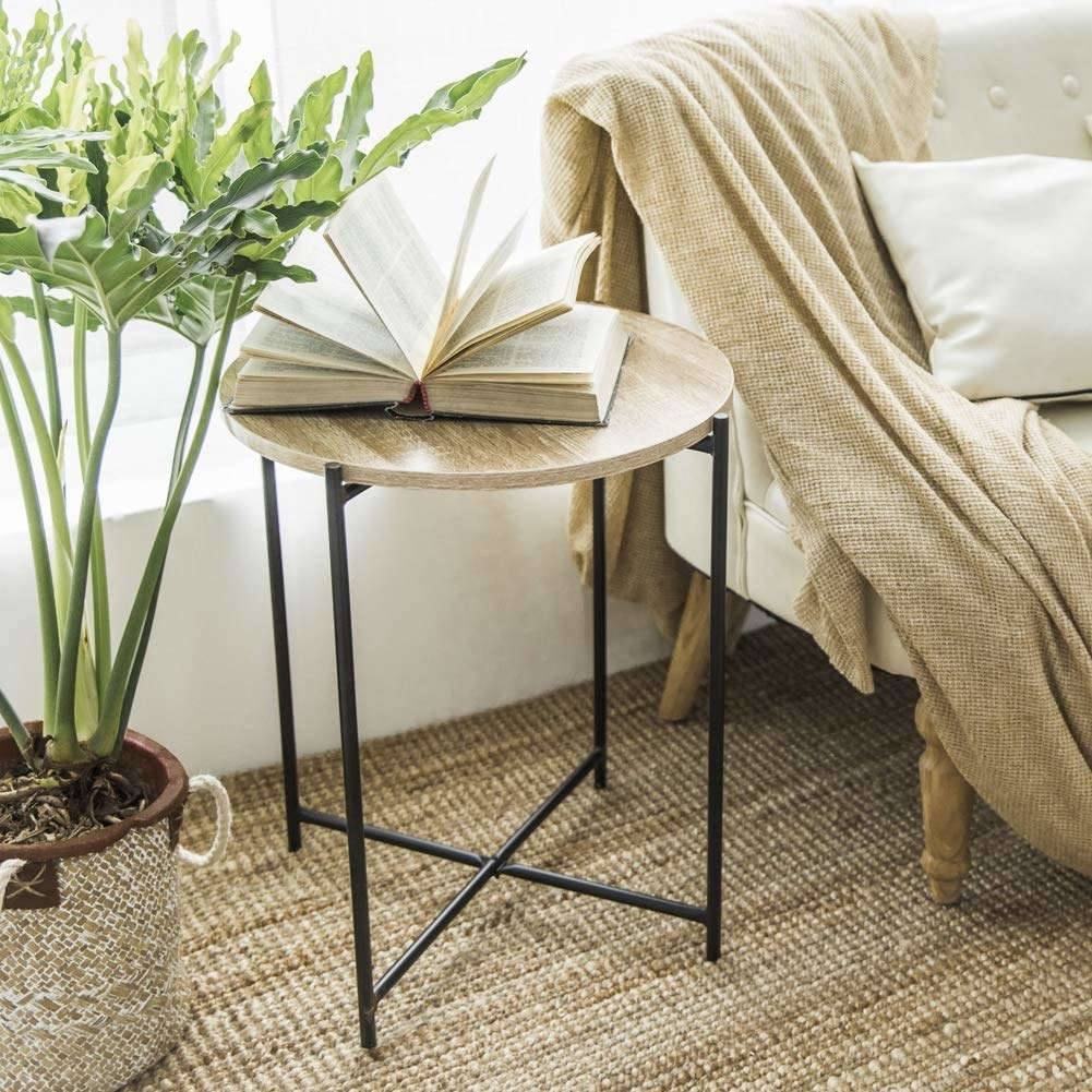 An accent table beside a sofa. The table has a light brown wooden top and black legs