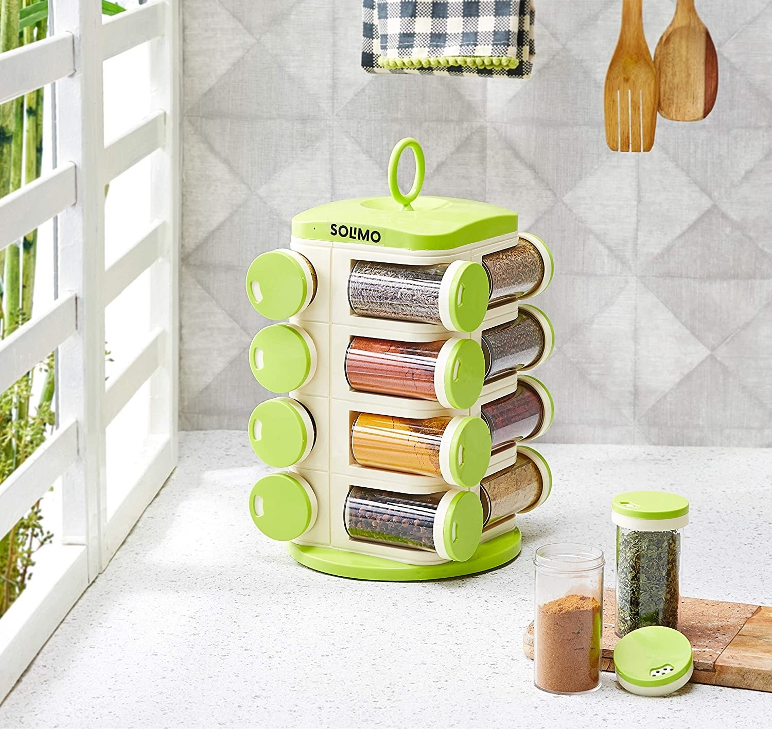 A rotating spice organiser with different spices in it next to spices on a chopping board