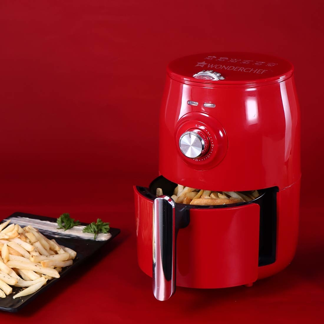 A bright red Air Fryer pictured with french fries in it.