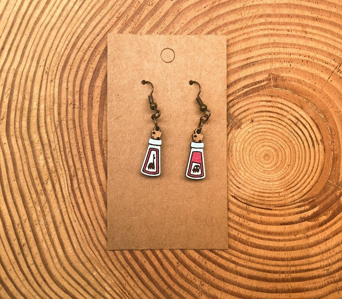 The pair of potion vial earrings, one with a little llama on it, the other with a skull