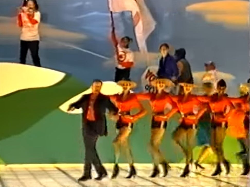 Robin Williams leading a string of dancers