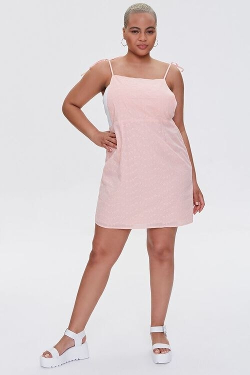 a model wearing the pink pinafore with white platform sandals