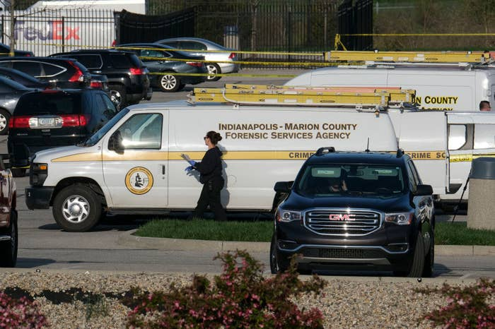 Vans from a forensic services agency are parked near an area that is cordoned off by police tape